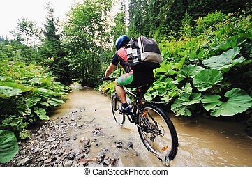 wetmtb - young man drive mountain bike over water river
