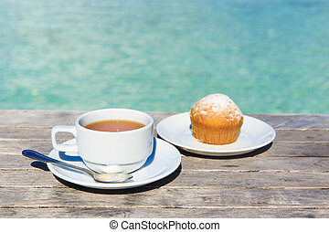 cup tea - A cup of tea on table with sea at the background