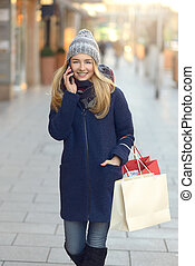Trendy young woman shopper using her mobile phone as she...