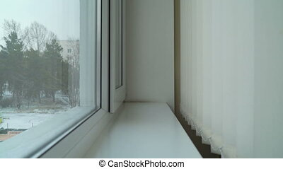 New window with vertical blinds and falling snow outside