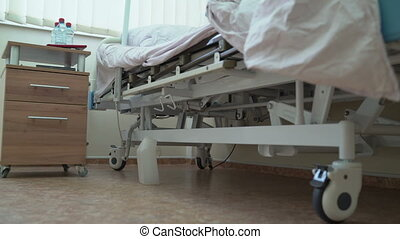 Man after surgery sitting on bariatric hospital bed in a patient room