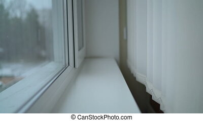 Window with vertical blinds and falling snow outside....