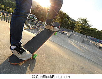people legs practice skateboarding at skatepark