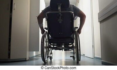 Rear view of disabled man pushes himself in wheelchair down...