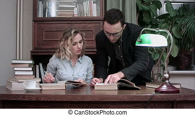 Young professor in glasses and female student discussing...