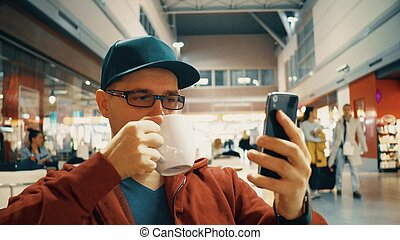 Man in black rim glasses watching video on his mobile phone and having big cup of coffee at the airport cafe