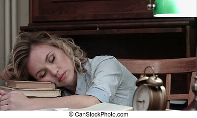 Pretty student fallen asleep on books at her desk and woken up by an alarm