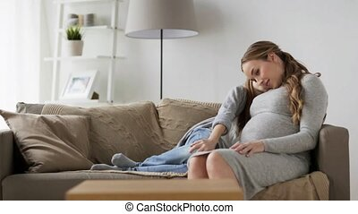happy pregnant woman and girl on sofa at home - pregnancy,...