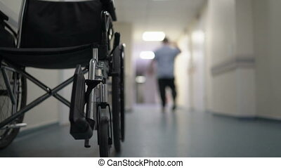 Hospital corridor with empty wheelchair and man walking...