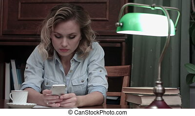 Serious young woman sitting at her workplace and typing an message on her phone