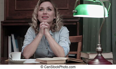 Happy young woman with hands clasped praying while sitting at desk in her home office