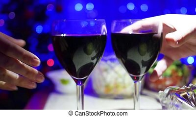 A couple holds of glasses of red wine and clink. In the background, bokeh lights and garlands of Christmas fir