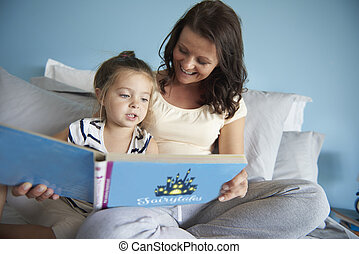 Mom and daughter reading some fairytales