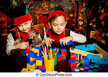 Little fairy elves make gifts for children at Christmas.