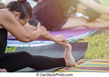 Asian woman doing yoga or exercise in the park - Group of...