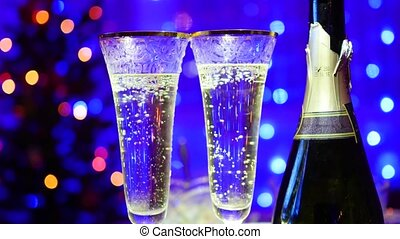 glasses with sparkling wine and bottle on bokeh background...
