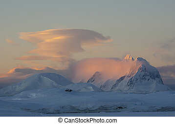 lenticular cloud at sunset over the mountains of the...