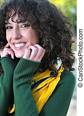 Young curly woman smiling outdoors in nature