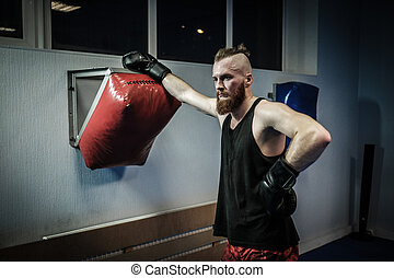 Fighter training with punching pad at gym.