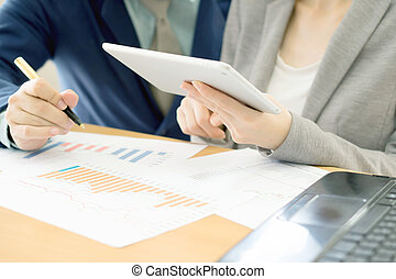 Young businesswoman explaining report to her colleague at meeting