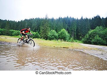 wet mount bike ride - young man drive mountain bike over...