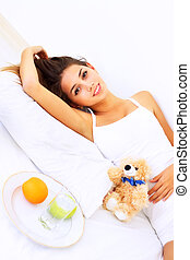 Beautiful girl lying on the bed with a teddy bear