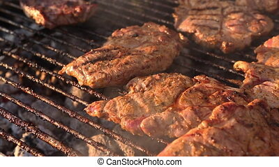 Barbecue grill with evening light - Closeup of rotating pork...