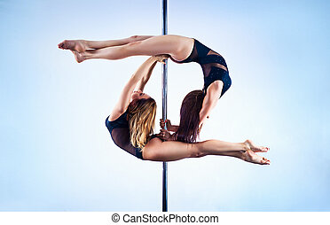 Pole dance team - Two young slim pole dance women on white...