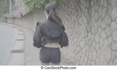 Pretty brunette fitness woman running outdoors - Back view...
