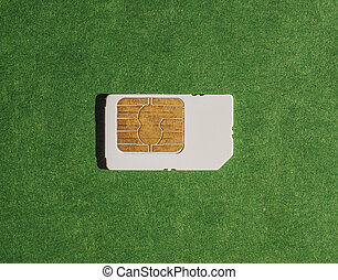 Telephone SIM card over green paper surface