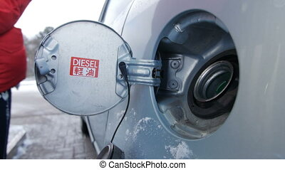Filling car with gas fuel at station pump. Blue car, winter....