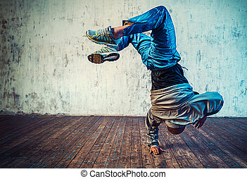 Man dancing on wall background - Young man break dancing on...