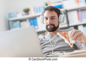 Man surfing the net and having a snack - Young man sitting...