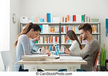 Hi-tech classroom - Group of college students doing homework...