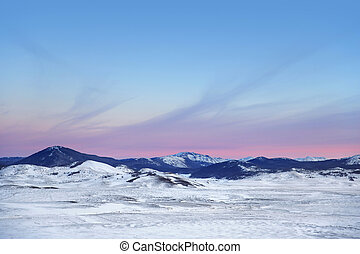 Winter landscape with mountains. Sunset sky. Snow day.