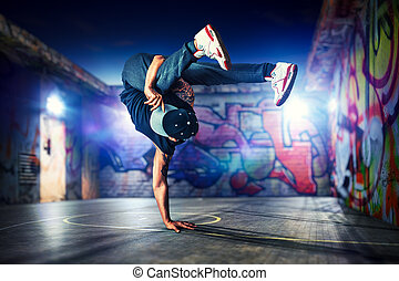 Break dancing outdoors - Young man break dancing at night on...