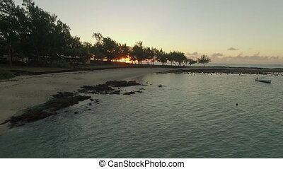 Aerial view of Mauritius coast and sunset over the ocean -...