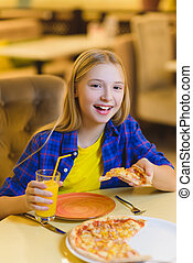 smiling girl eating pizza and drinking juice indoor.