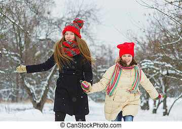 two happy girls playing on the snow in winter day outdoor