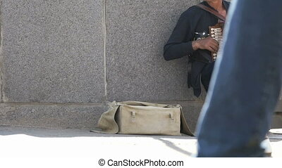 Tanned man aged 60s plays the accordion outdoors - Tanned...