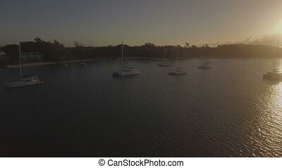 Flying over yachts along the coast at sunset - Aerial view...