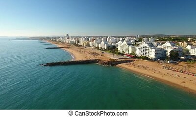 Aerial. Video Beach sky with breakwaters Quarteira town....