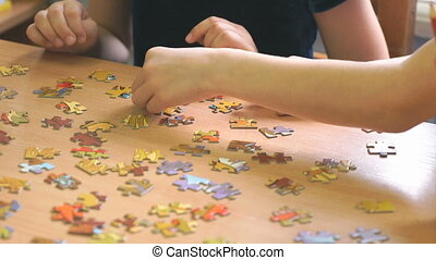 Two preschool girls play a game collecting puzzles - Two...