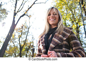 Cute young woman smiling outdoors in nature
