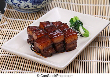 Stewed pork meat in chinese style on white plate on bamboo...