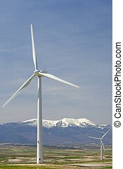 wind energy - wind mills and snowy mountain with blue sky
