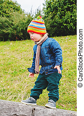 Adorable toddler boy playing in park, wearing colorful hat,...