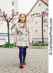 Little girl walking down the street, wearing beige coat,...