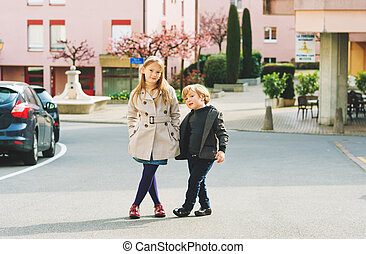 Two fashion kids models posing outdoors on nice spring day,...