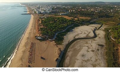 Aerial. Beach and lake a dried, town Quarteira, filmed from...